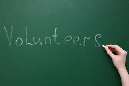 Woman writing word VOLUNTEERS on green chalkboard Stock Photo