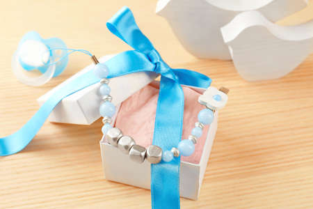 Cute pacifier clip with place for baby name in gift box on table Stock Photo