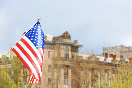 Waving USA flag and blurred building on background