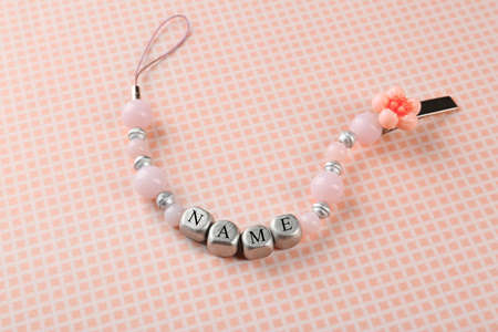 Beautiful pacifier clip with place for baby name on table Foto de archivo