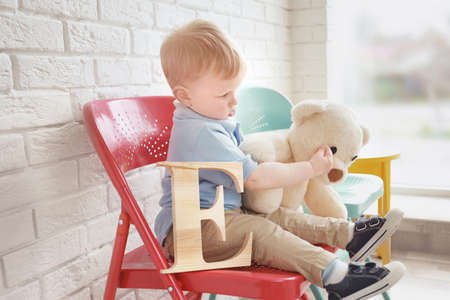 Cute little boy with letter E sitting on chair at home Stock Photo