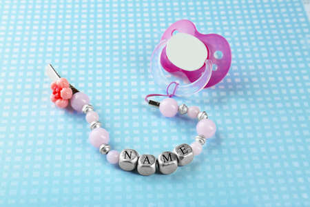 Pacifier clip with place for baby name and dummy on table
