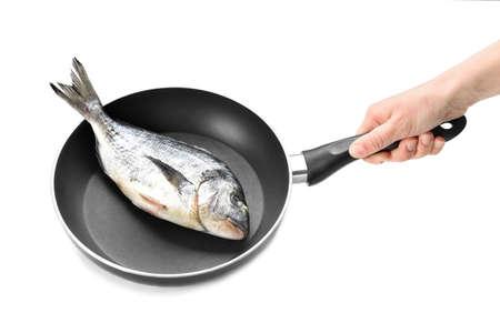 Female hand holding frying pan with fresh dorado fish on white background Stock Photo