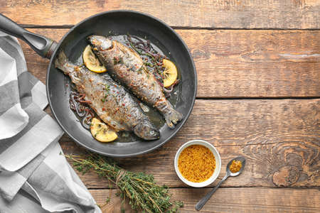 Composition with tasty fried trout fish on wooden background