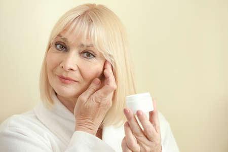 Senior woman applying cream onto face against light background Foto de archivo