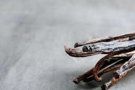 Dried vanilla sticks on grey textured background, closeup
