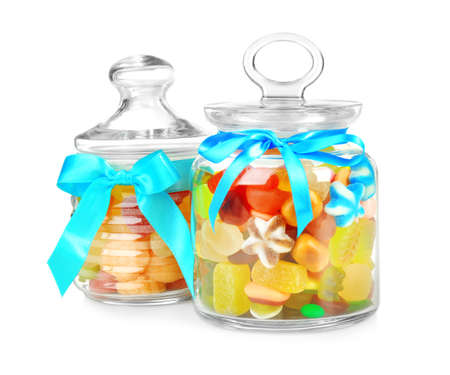 Different candies in glass jars on white background