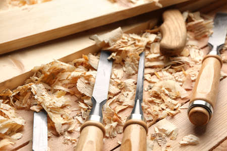 Carpenters tools, boards and saw dust on wooden table in workshop, closeup