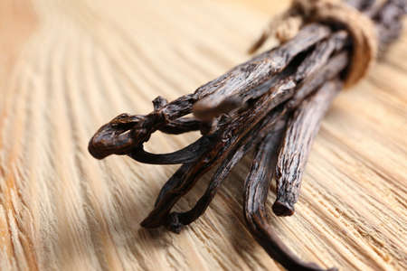 Dried vanilla sticks on wooden background, closeup Banco de Imagens