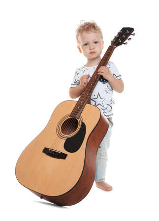 Cute little boy with acoustic guitar on white background Stock Photo