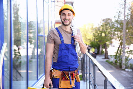 Young smiling electrician holding bunch of wires outdoors Reklamní fotografie