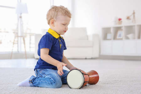 Cute little boy with drum on floor at home