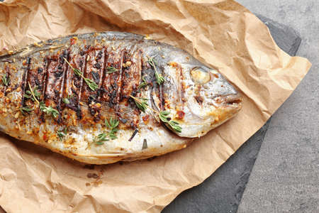 Paper with delicious fried fish on table