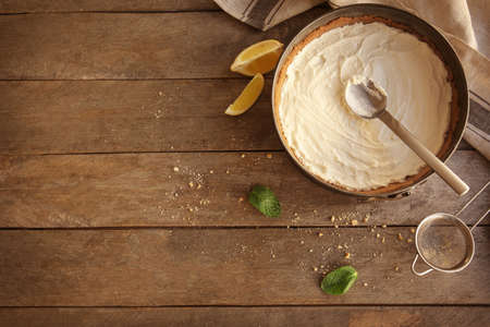 Baking pan with raw cheese cake and spoon on kitchen table Stok Fotoğraf