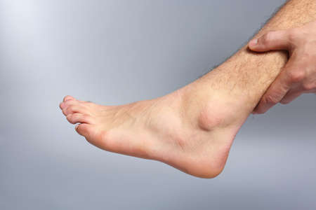 Young man suffering from pain in leg on grey background, closeup