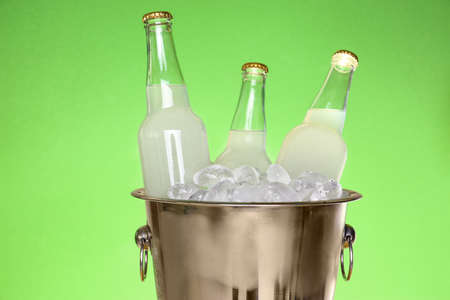 Bottles of lemonade in bucket with ice on green background