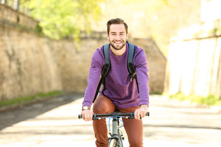 Handsome young man riding bicycle outdoors on sunny day Stock Photo