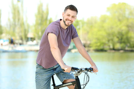 Handsome young man with bicycle outdoors on sunny day Stock Photo