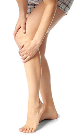 Young woman suffering from pain in leg on white background