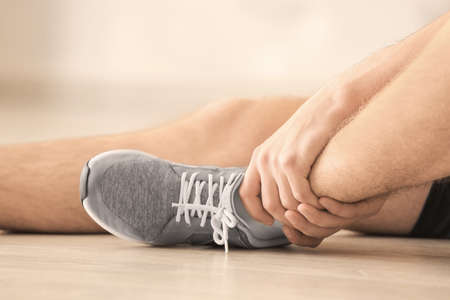 Young man suffering from pain in leg while sitting on floor indoors, closeup