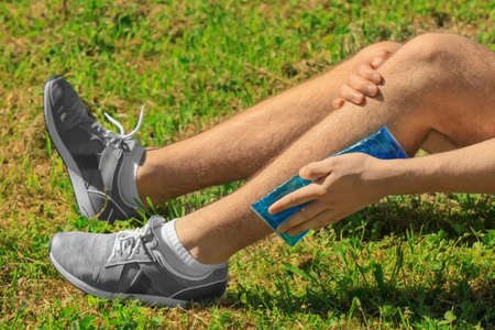 Young man applying cold compress to leg while sitting on grass outdoors, closeup Stock Photo