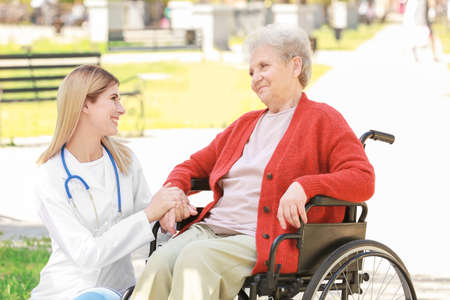Young nurse and disabled elderly woman in wheelchair outdoors on sunny day