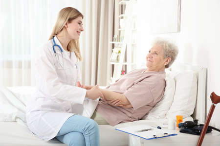 Young nurse examining elderly woman at home