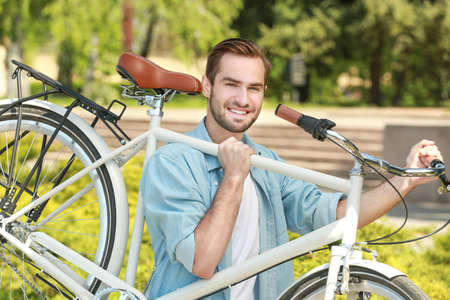 Handsome young man carrying bicycle outdoors Stock Photo