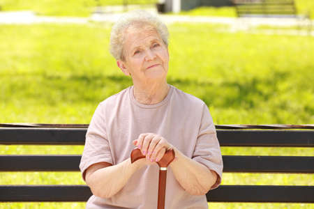 Elderly woman with cane sitting on bench in park