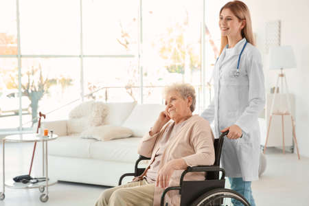 自宅で車椅子に乗った若い看護師と障害のある高齢女性