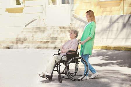 Disabled elderly woman and young caregiver outdoors on sunny day