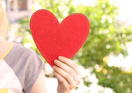 Woman holding red heart on blurred background. Volunteer concept Stock Photo