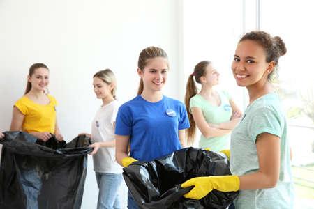 Giovani volontari con sacchi della spazzatura al chiuso Archivio Fotografico