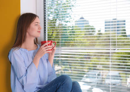 Beautiful young girl looking in window and holding cup of coffee or tea in hands