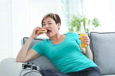 Mature woman sitting on sofa with hamburger, soda and video game console. Sedentary lifestyle concept
