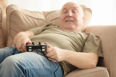 Fat senior man playing videogame while lying on sofa at home, closeup. Sedentary lifestyle concept