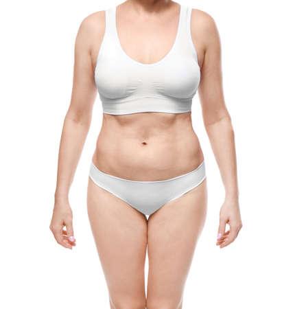 Mature woman in underwear on white background. Weight loss concept Standard-Bild