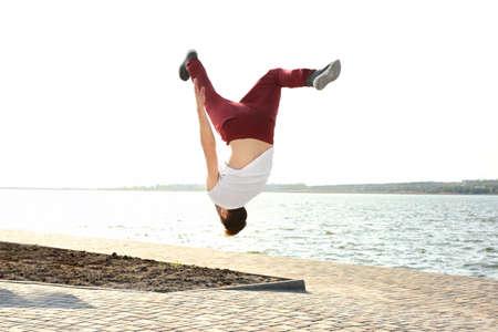 jeune homme sportif faire des exercices acrobatiques près de la rivière
