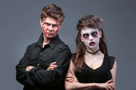 Young man and woman with Halloween makeup on grey background