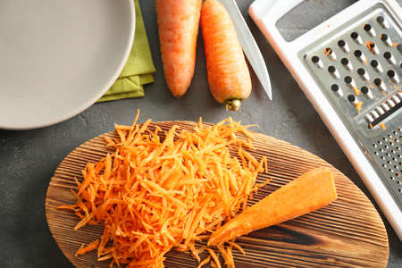 Wooden board with heap of grated carrot on kitchen table