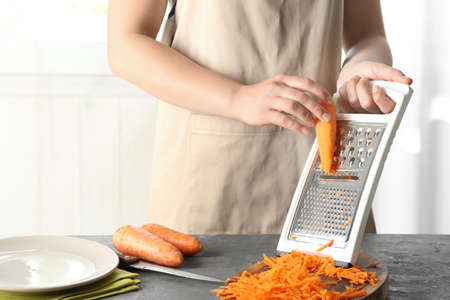 Woman grating carrot on kitchen table