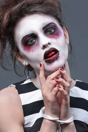 Young woman with Halloween makeup and tied hands on grey background, closeup