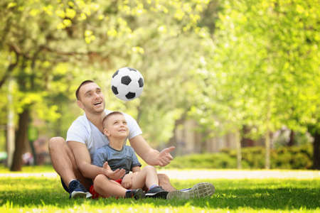 Father and son playing with soccer ball while sitting on green grass in park