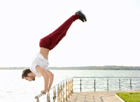 Young sporty man doing acrobatic exercises near river
