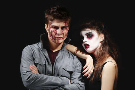 Young man and woman with Halloween makeup on dark background Stock fotó
