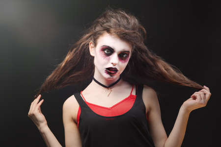Young woman with Halloween makeup on dark background