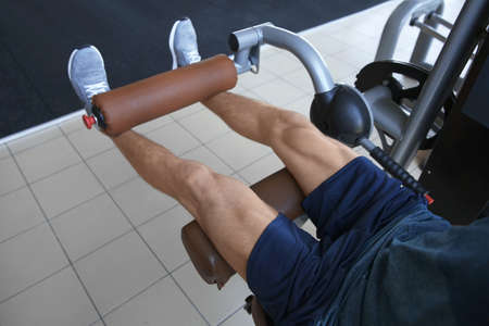 Sporty young man training legs in gym, closeup