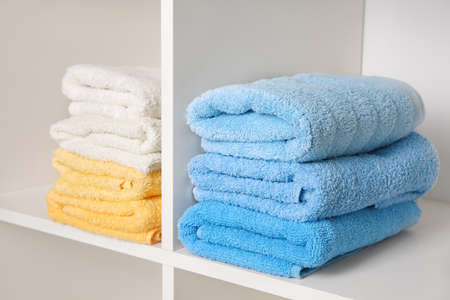 Stacks of clean fresh towels on shelves Stock Photo