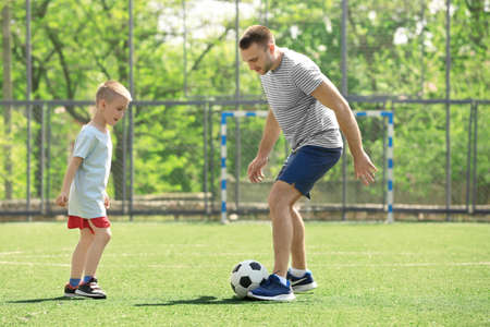 Father and son playing football on soccer pitch Stock Photo