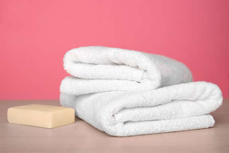 Clean towels on table against color background Stock Photo